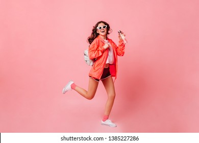 Sports girl in windbreaker, shorts and sneakers runs on pink background. Woman in sunglasses holding bottle of water