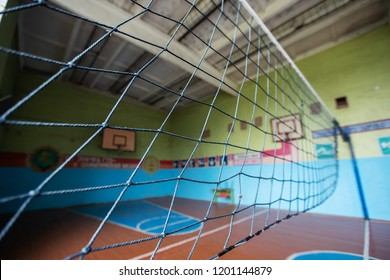 sports hall for school competitions, no one in classroom, preparing a game of volleyball, texture background, rope net for the match stretched between the walls, throw ball, leisure and excitement