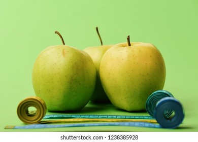 Sports and healthy lifestyle symbols. Apples near rolled measuring tapes on green background, close up. Diet and sport regime concept. Pattern made of apple fruits near blue and yellow tape measures