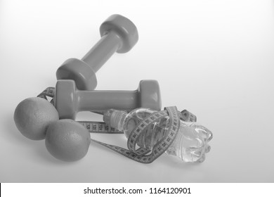 Sports and healthy regime, copy space. Dumbbells in green color, water bottle, measure tape and fruit on white background. Barbells made of plastic near juicy oranges. Diet and sport regime concept