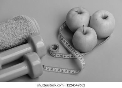 Sports and healthy regime equipment, copy space. Barbells near juicy green apples. Athletics and weight loss concept. Dumbbells in bright green color, measure tape, towel and fruit on green background