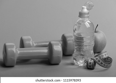 Sports and healthy regime equipment. Diet and sport regime concept. Dumbbells in green color, water bottle, measure tape and fruit on green background. Barbells near juicy apple and blue tape.