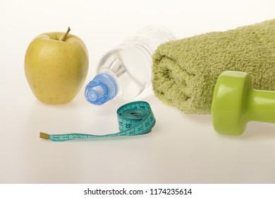 Sports and healthy regime equipment. Diet and sport regime concept. Barbell made of plastic near green apple. Dumbbell in green color, water bottle, measure tape, towel and fruit on grey background