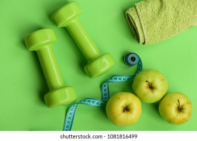 Sports and healthy regime equipment, top view. Athletics and weight loss concept. Dumbbells in green color, twisted measure tape, towel and fruit on green background. Barbells near juicy green apple