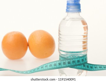 Sports and healthy regime symbols, copy space. Water bottle wrapped with measure tape and fruit on light grey background. Diet and healthy regime concept. Orange fruits near bottle of refreshing water