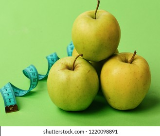 Sports and healthy regime symbols. Diet and sport regime concept. Apples in bright green color and twisted measure tape on green background. Tape measure in cyan color near juicy fruit, close up