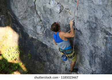 Sports images of a lean muscled rock climber on a broad limestone cliff.  He is sport climbing with safety gear: a rope, quickdraws, harness and chalk bag.  It is a bright sunny summer day.
