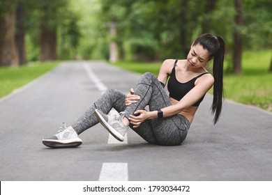 Sports injury. Asian Female Athlete Suffering From Ankle Trauma Pain After Jogging In Park, Free Space