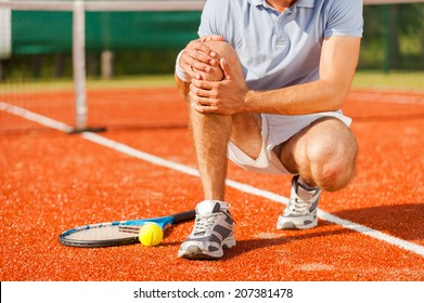 Sports injury. Close-up of tennis player touching his knee while sitting on the tennis court