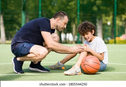 Sports Injury. Handsome PE teacher helping boy with knee trauma after playing basketball