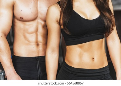 Sports joint . A guy and a girl at the gym . Naked belly - press.Guy tattoo , and the girl is Asian