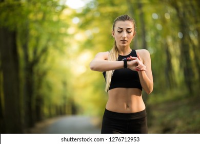 Sports lifestyle, autumn. Beautiful, young girl in sportswear looking fitness tracker, smart watch after jogging, playing sports in the park, forest