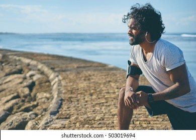 Sports lifestyle. Happy young african man exercising on the sea shore. Tired after jogging.