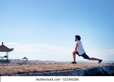 Sports lifestyle. Happy young african man stretching on the sea shore.