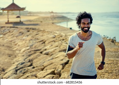 Sports lifestyle. Happy young african man jogging on the sea shore.