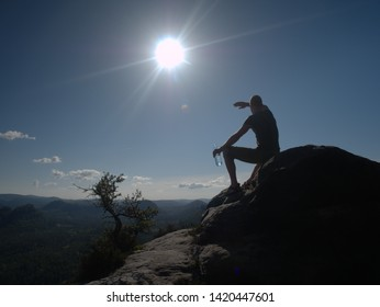 Sports man drinking water from plastic bottle in beautiful mountains during sunset. Trekking concept