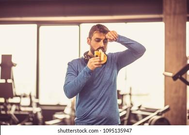 Sports man eating banana during training in gym.