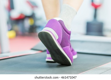 sports man in a gym on treadmill in sport shoes