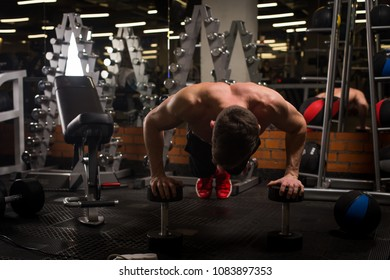A sports man performs exercises in the gym for muscle pumping