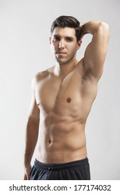 sports man posing half naked on grey background