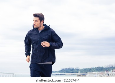Sports man running at the morning outdoors