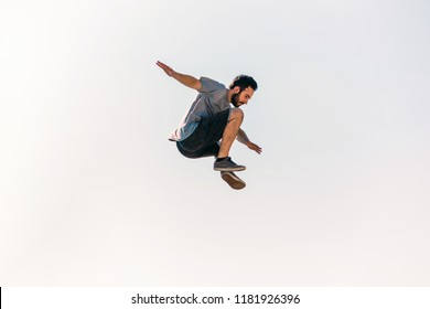 Sports man training parkour while jumping in the air