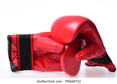 Sports and martial arts concept. Boxing gloves in red color isolated on white background. Leather box equipment for fight and training. Pair of boxing gloves lying next to each other.