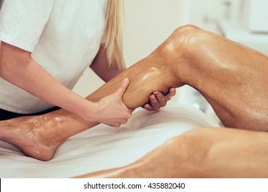 Sports massage - Calf massage - Physical therapist doing massage of calfs. Toned image, selective focus.