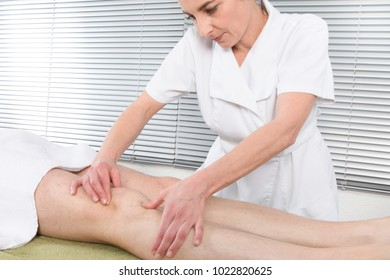 Sports massage. Female physical therapyst massaging leg of male athelete