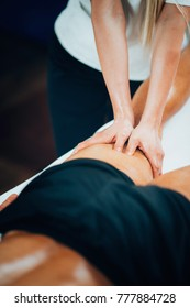 Sports massage. Female physical therapyst massaging leg of male athelete