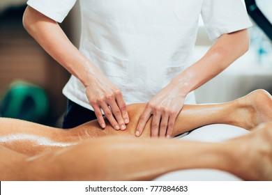 Sports massage. Physical therapyst massaging leg of young male athelete