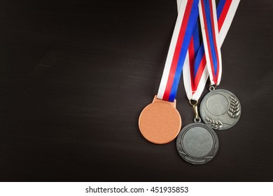 Sports medals on a wooden background. Collection of medals for the winners. Awards in sports.