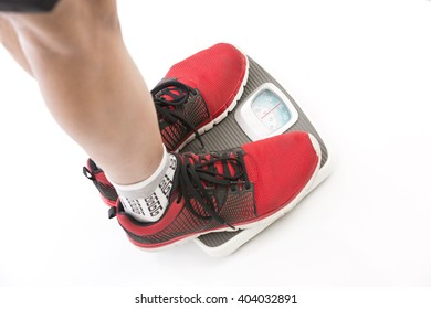 Sports men feet standing on weighing scale on white background.