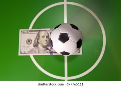 Sports and money concept - Toy soccer ball in a midfield, in the center of the green field and the banknote in hundred dollars on a background