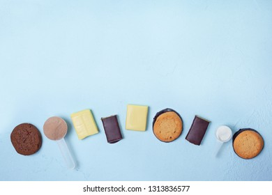 sports nutrition: protein bars, protein biscuits, protein powder on a blue background. view from above. copy space