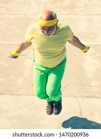 Sports old man doing exercises with jumping rope. Healthcare cheerful lifestyle. Age is no excuse to slack on your health