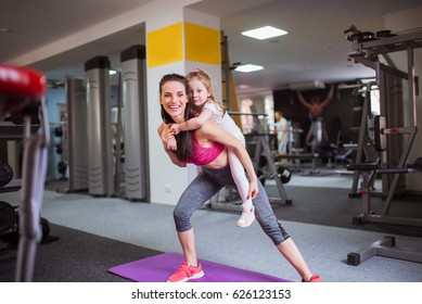 Sports older sister keeps on back her little sister and do exercise together, at the gym