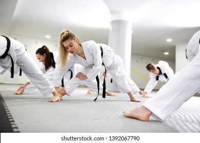 Sports and para-sports athletes training martial art of taekwondo together, stretching concept