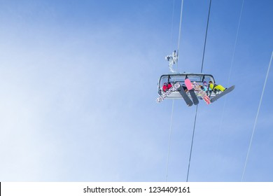sports people on the chairlift in a ski resort among snow-capped mountains