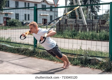 A sports person,  the fresh air is engaged  training trx,  sports clothes,  the summer the city, wringing out. Strength and stamina motivation.