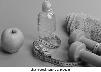 Sports regime equipment, close up. Barbells near juicy green apple. Dumbbells in bright green color, water bottle, measure tape, towel and fruit on green background. Athletics and weight loss concept.