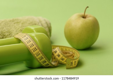 Sports regime equipment, close up. Athletics and weight loss concept. Dumbbells in bright green color, measure tape, towel and fruit on green background. Barbells by juicy green apple