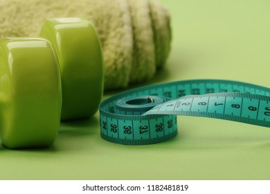 Sports regime equipment. Dumbbells in green color, twisted measure tape and towel on green background, defocused. Tape measure in cyan color by barbells, close up. Athletics and weight loss concept