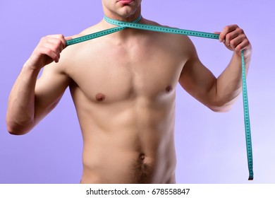 Sports regime idea. Man with naked torso ties measuring tape around his neck. Young sportsman with cyan flexible ruler on light purple background. Diet and healthy lifestyle concept.