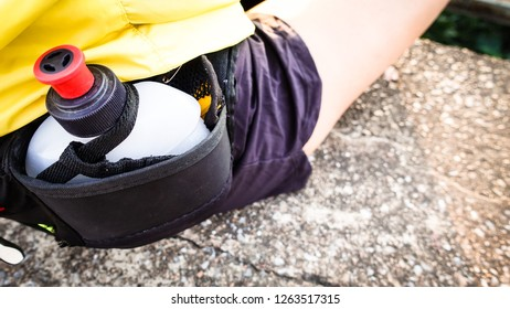 Sports running bag on the belt  with a jar for water with runner sitting on the road