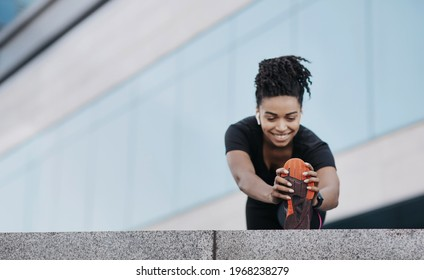 Sports, running, exercises to keep fit and lose weight in city after covid-19. Happy young african american woman in sportswear and wireless headphones doing leg stretch on city building background