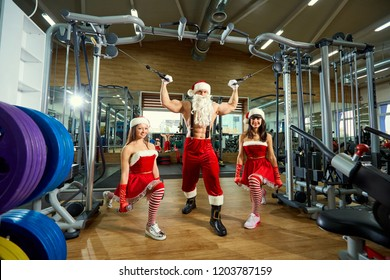 Sports Santa Claus with girls in Santa's costumes in the gym.