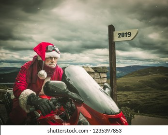 Sports Santa Claus in a hurry in 2019 on a red motorcycle against the backdrop of the winter landscapeю