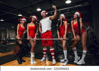 Sports Santa Claus taking selfie by mobile phone with girls in Santas costumes in the gym