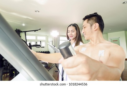 Sports scientist lady tablet physical examination athlete in the fitness room.